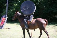 Tjäna som soldat i historiska kläder på hans häst med målet och arro Arkivbild