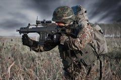 Tjäna som soldat med den militära hjälmen och vapnet i handling Fotografering för Bildbyråer