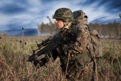 Tjäna som soldat med den militära hjälmen och vapnet i handling Arkivbild