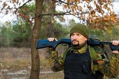 Tjäna som soldat med ett gevär i höstskogen Royaltyfri Foto