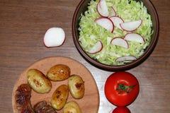 Tjäna som tabellen med nya potatisar Arkivfoto