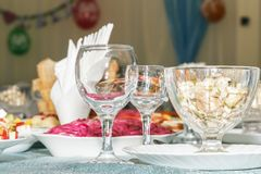 Tjänad som banketttabell med suddig bakgrund i restaurang Tomma vinexponeringsglas, grönsaksallad och skivad fruktcloseup Sida VI Royaltyfri Bild