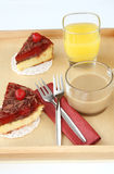 Tjänad som romantisk frukost för två: koppen kaffe, exponeringsglas av orange fruktsaft och läcker körsbärsröd ost bakar ihop Royaltyfri Foto