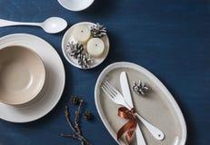 Tjänad som tabell för jullunch mat Tomma plattor, bunkar, gaffel, kniv, sked, julgarneringar, kottar och stearinljus på blå woode Arkivfoton