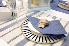 Tjänad som tabell med blåttdisk på en blå vit bordduk, havsskal Royaltyfria Foton