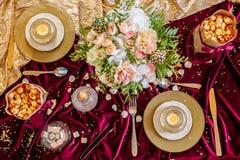 Tjänad som tabell med buketten och stearinljus Arkivbild