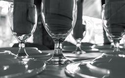 Tjänad som tabell med exponeringsglas Ren diningware på det svartvita fotoet för tabell Arkivfoton