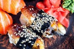 Tjänade som den fastställda sashimien för sushi och sushirullar på den mörka plattan Bild av japansk mat på mörk bakgrund Royaltyfria Bilder