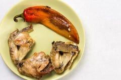 Tjänade som lekmanna- ovannämnda stekt kycklingvingar för lägenhet med stekt paprika på plattan ovanför vitmarmortabellen Royaltyfri Bild