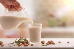 Tjänande som exponeringsglas av mandeln mjölkar på den vita tabellen i kök royaltyfri bild