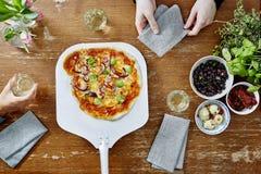 Tjänande som läcker vegetarisk pizza till hungriga gäster Arkivbilder