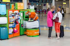Tjänaren packar bagage av passagerare, innan han stiger ombord en nivå Inre sikt av Vladivostok den internationella flygplatsen royaltyfri fotografi