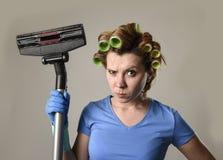 Tjänste- kvinna för hembiträde eller rubbninghemmafru i hårrullar som gör ren G Arkivfoton
