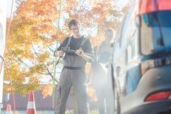 Tjänste- manportionkvinna som gör ren hennes automatisk i biltvätt arkivfoton
