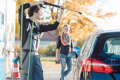 Tjänste- manportionkvinna som gör ren hennes automatisk i biltvätt royaltyfri bild