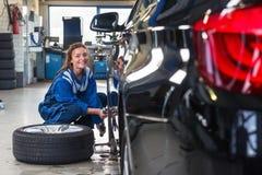 Tjänste- mekaniker för kvinnlig som ändrar det främre gummihjulet av en bil arkivfoto