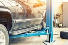 Tjänste- mitt för bil Det gamla rostiga offroad SUV medlet lyftte på elevator på underhållsstationen Bilreparation och kontroll u arkivfoto