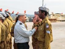 Tjänstemän av IDFEN belönar soldaten med gradbeteckningen på bildandet i stupad minnes- monument för teknikkår i Mishmar Arkivfoto