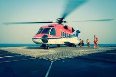 Tjänstemannen tar omsorgpassageraren för att gå ombord helikoptern på oljeplattformen Royaltyfria Bilder