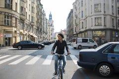 Tjeckien Prague 11 04 2014: Ung flicka som cyklar i capitolstadskvinnlign som kyler på en solig dag Royaltyfri Bild