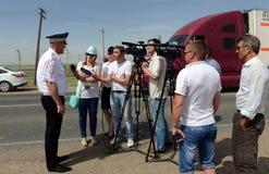 Tjänstemannen av vägpatrullservice ger intervjuer till journalister Arkivbilder
