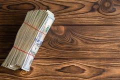 Tjock bunt av använt 100 dollarräkningar på lantligt trä Fotografering för Bildbyråer