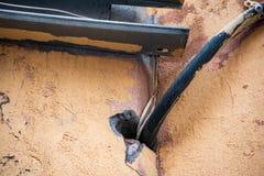 Tjock kabel och trådar i hålet i väggen royaltyfri foto