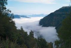 Tjock molnräkning i en alpin dal arkivbild