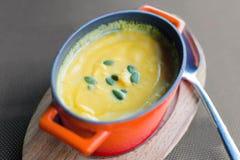 Tjock pumpakräm-soppa i en miniatyrröd järn- kruka på en träställning Tjäna som i ett kafé royaltyfria bilder