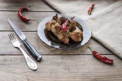 Tjock skiva av nötkött med kryddor och glödhet chilipeppar på plattan, kniv, gaffel på träbakgrund royaltyfri foto