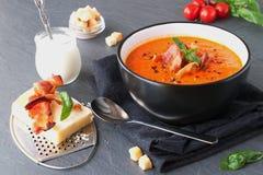Tjock tomatsoppa med basilika och stekt bacon i en svart keramisk bunke på en grå abstrakt bakgrund äta som är sunt Arkivfoton