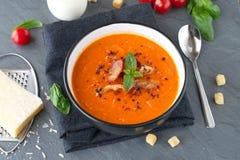 Tjock tomatsoppa med basilika och stekt bacon i en svart keramisk bunke på en grå abstrakt bakgrund äta som är sunt Fotografering för Bildbyråer