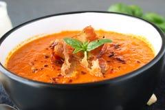 Tjock tomatsoppa med basilika och stekt bacon i en svart keramisk bunke på en grå abstrakt bakgrund äta som är sunt Arkivfoto