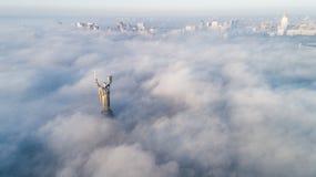 Tjocka moln av h?stdimma och f?derneslandmonumentet som klibbar ut ur dem royaltyfri fotografi