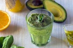 Tjocka näringsrika smoothies, som inkluderar: avokado, äpple, banan, spenat, orange fruktsaft, honung, linfrö, mintkaramell och o royaltyfri foto