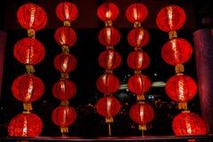 Tjugotre röda kinesiska lykta med en bild som hänger i dörröppningen och ljuset i natten Singapore Royaltyfri Bild