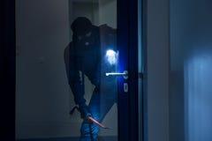 Tjuv With Flashlight Trying som bryter dörren arkivfoto