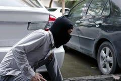 Tjuv i den svarta balaclavaen som försöker att bryta in i bilen royaltyfri fotografi