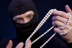 tjuv Man i svart maskering med en pärlemorfärg halsband royaltyfri fotografi