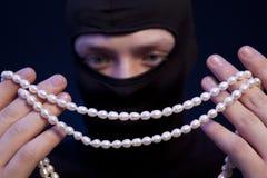 tjuv Man i svart maskering med en pärlemorfärg halsband royaltyfria foton