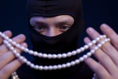 tjuv Man i svart maskering med en pärlemorfärg halsband royaltyfri bild