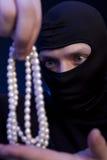 tjuv Man i svart maskering med en pärlemorfärg halsband royaltyfria bilder
