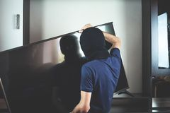 Tjuv med den svarta balaclavaen som stjäler modern dyr television royaltyfria foton