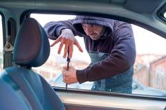 Tjuv som bryter bilfönstret för att stjäla en bil royaltyfri bild