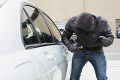 Tjuv som bryter in i bilen med skruvmejsel Arkivfoton