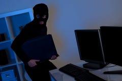Tjuv som stålsätter en dator Arkivfoto
