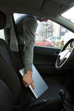 Tjuv som stjäler bärbara datorn till och med bilfönster Arkivfoto