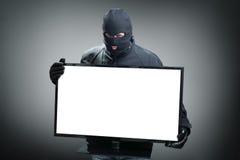 Tjuv som stjäler datorbildskärmen Fotografering för Bildbyråer