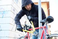 Tjuv som stjäler en cykel i stadsgatan royaltyfri bild