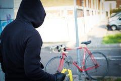Tjuv som stjäler en parkerad cykel i stadsgata royaltyfri foto